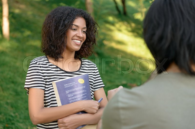 Stock image of 'Image of multiethnic young students studying outdoors while talking. Looking aside.'