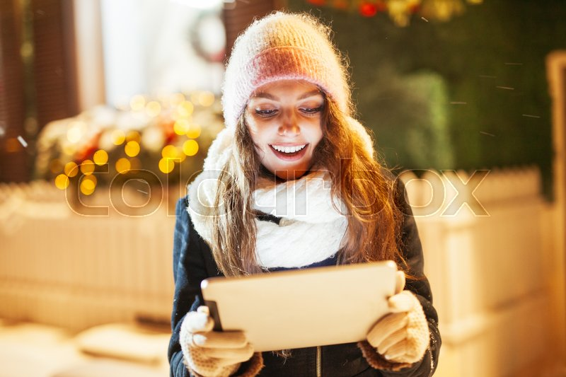 Stock image of 'Young woman using tablet computer on the street.'