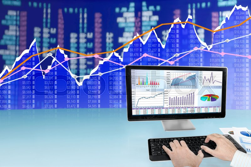 Stock image of 'Man analyzing financial data and charts on computer'