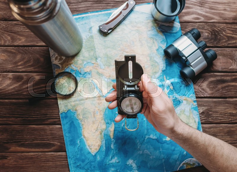 Stock image of 'Man holding a compass over a map and planning to travel, point of view. Focus on the compass. The map is blurred'