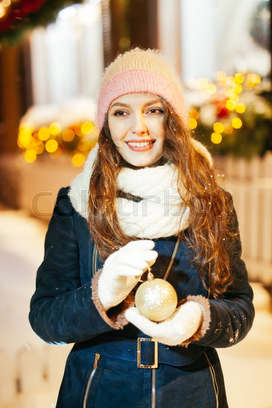 Stock image of 'Female hands holding a Christmas gold ball. Frosty winter day in snowy forest. Merry Christmas and Happy New Year theme'