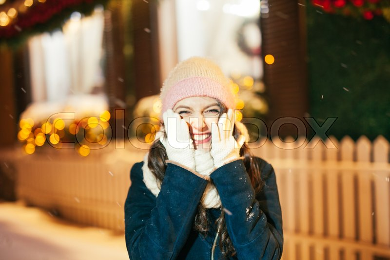 Stock image of 'Happy winter time in big city of charming girl walking on street in coat with backpack. Enjoying snowfall, expressing positivity, smiling to camera, joyful cheerful mood, true emotions, new year mood'
