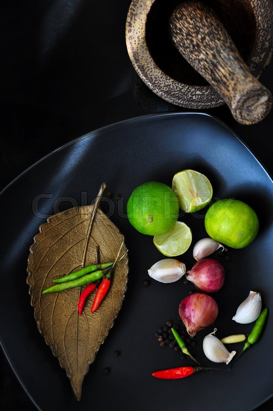 Stock image of 'Top view of spice ingredients with mortar on black background'
