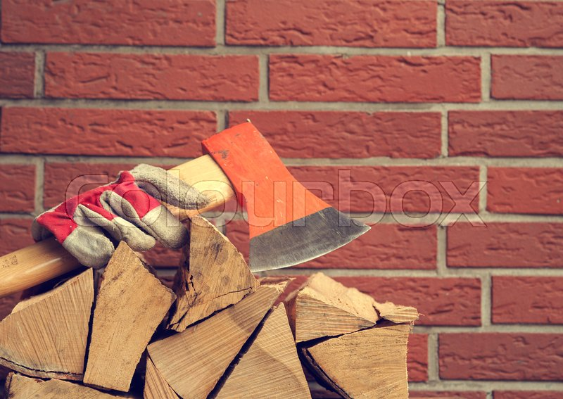 Stock image of 'Stacked beech fire wood with an axe and working gloves on a red brick wall with space for text or image, retro stylized'