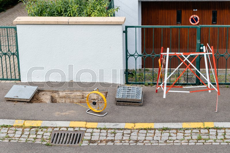 Stock image of 'Open sewage manhole hole with yellow fiber cable on coil spool - telecommunication internet provider company working on implementation of fiber optic cables in city '
