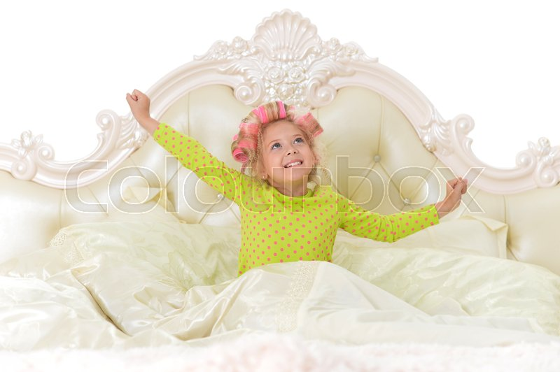 Stock image of 'Portrait of cute little girl with pink hair curlers on head'