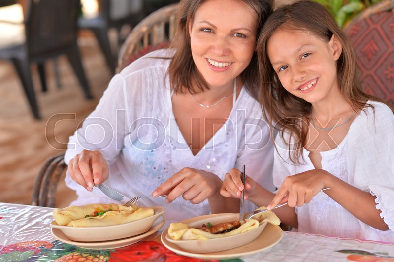 Stock image of 'happy mother and daughter eating in cafe together'