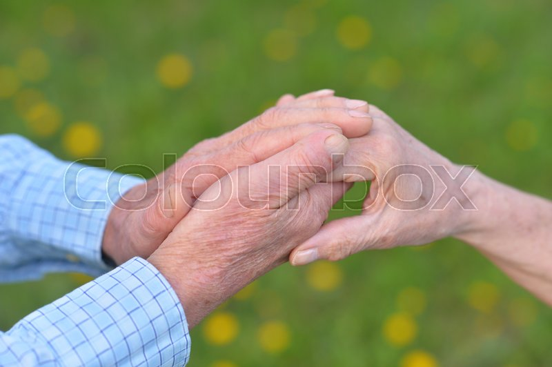 Stock image of 'Close up view of senior couple holding hands together'