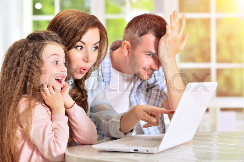 Stock image of 'Happy family sitting at table with laptop'