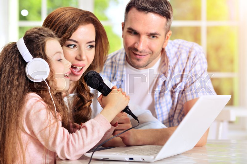 Stock image of 'Happy family sitting at table with laptop and singing karaoke'