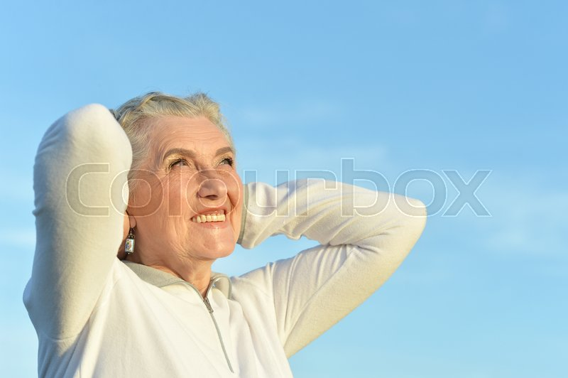 Stock image of 'Portrait of beautiful senior woman against blue sky'