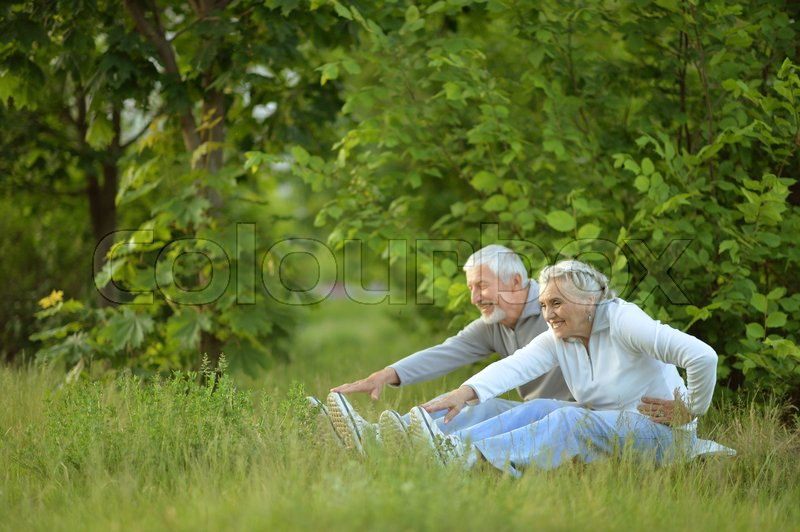 Stock image of 'Portrait of a happy senior couple doing exercises outdoors'