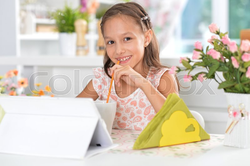 Stock image of 'Cute girl sitting at kitchen with digital tablet'