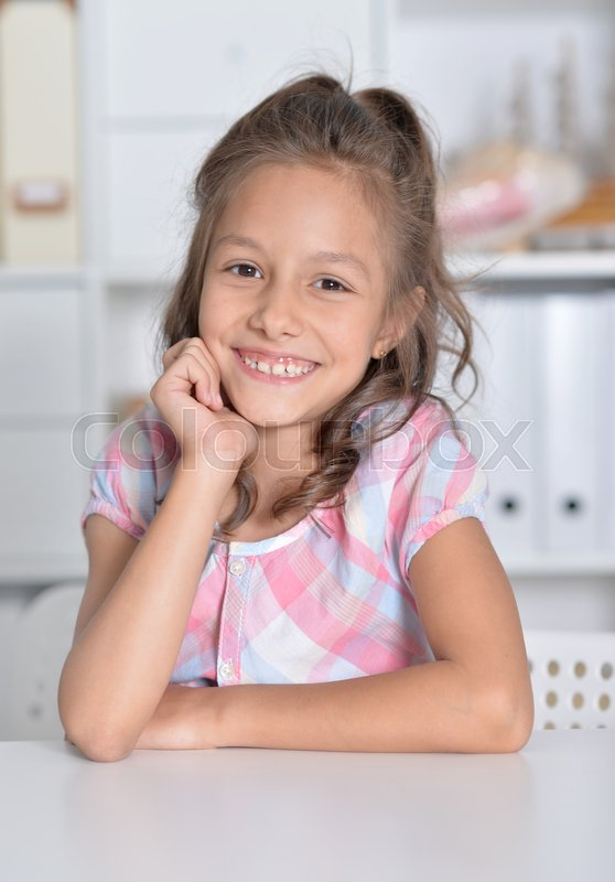 Stock image of 'Portrait of cute girl sitting at table'