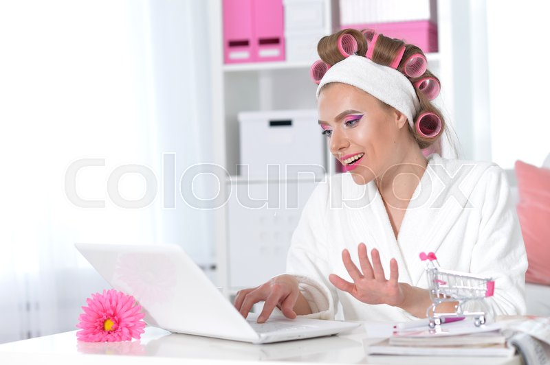 Stock image of 'Beautiful young woman in white bathrobe sitting at table with laptop and making online shopping'