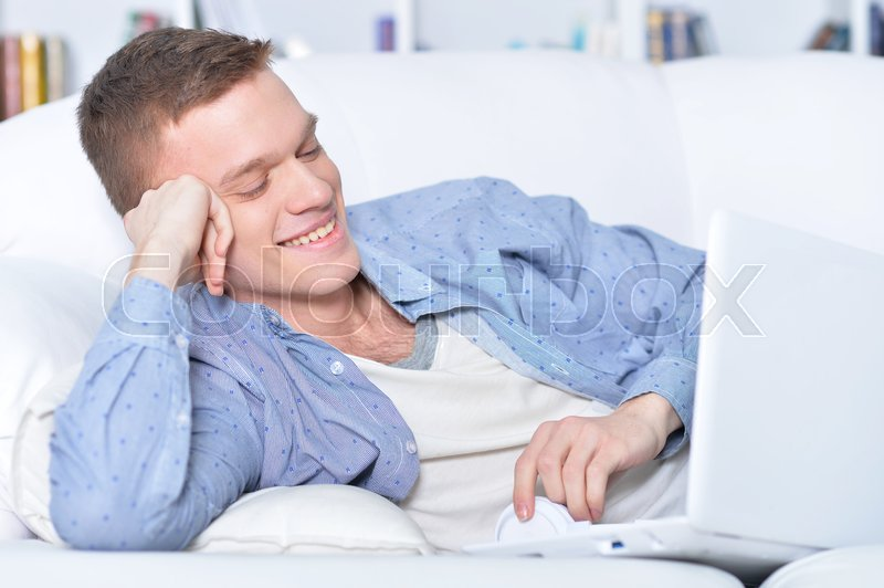 Stock image of 'handsome young man lying on white couch with laptop'
