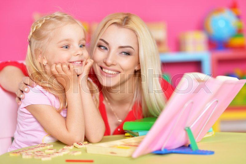 Stock image of 'Mom helps a little daughter to do homework'