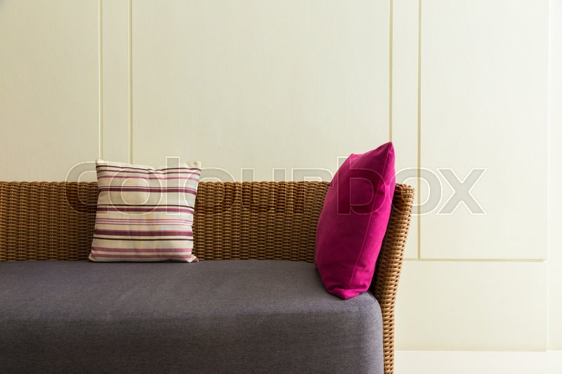 Stock image of 'section of empty modern design wicker sofa with 2 pillows and empty wall, room for text or copyspace '