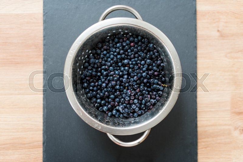 Stock image of 'Colander with freshly washed organic blueberries on grey slate stone board.'