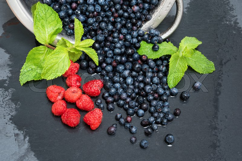 Stock image of 'Fresh washed raspberries, blueberries, mint leaves with waterdrops. Organic berries on grey slate stone board.'