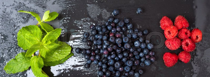 Stock image of 'Fresh washed raspberries, blueberries, mint leaves with waterdrops. Organic berries on grey slate stone board. Smoothie ingredients. Banner for website.'