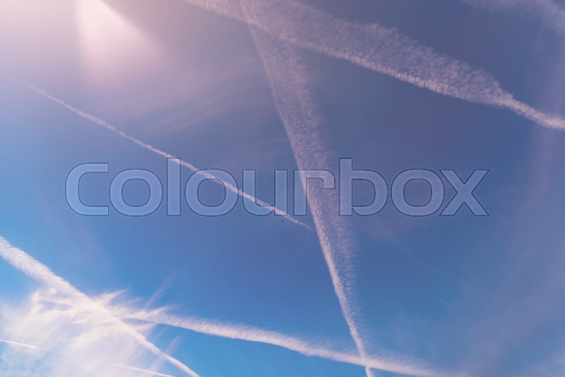 Stock image of 'Jet airplane trails contrails in blue sky'