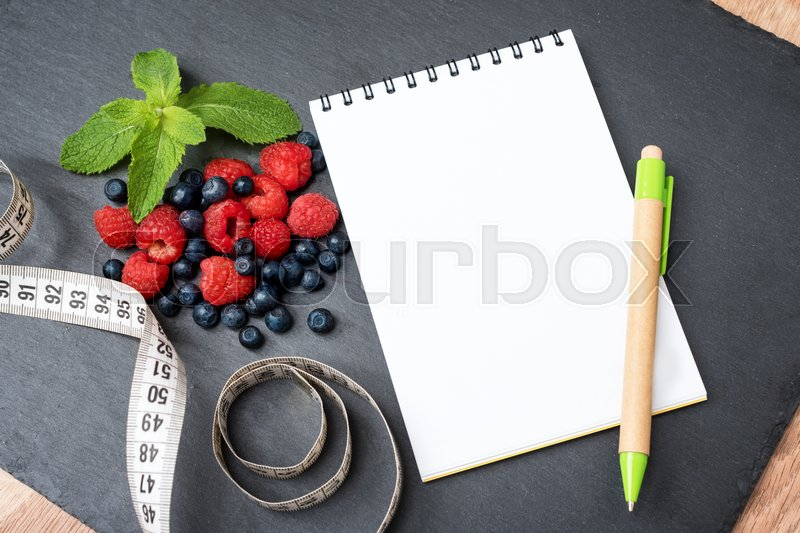 Stock image of 'Blueberries, raspberries, mint, measuring tape and notepad for writing notes or resolutions, concept of sport, diet, slimming, detox, healthy lifestyles and nutrition. Mock up, space for text.'
