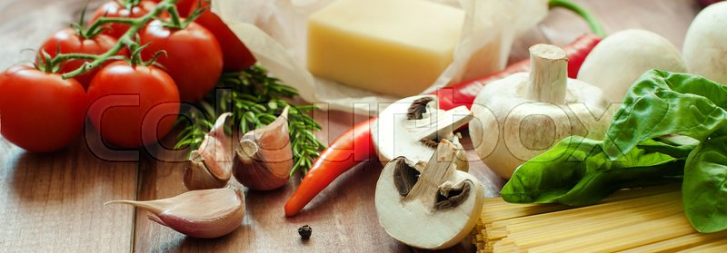 Stock image of 'Italian food or ingredients background with fresh vegetables, pasta, cheese parmesan and spices. Top view, view from above. Copy space. Dark background. banner'