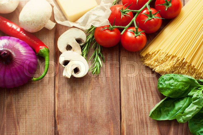 Stock image of 'Italian food or ingredients background with fresh vegetables, pasta, cheese parmesan and spices. Top view, view from above. Copy space. Dark background.'