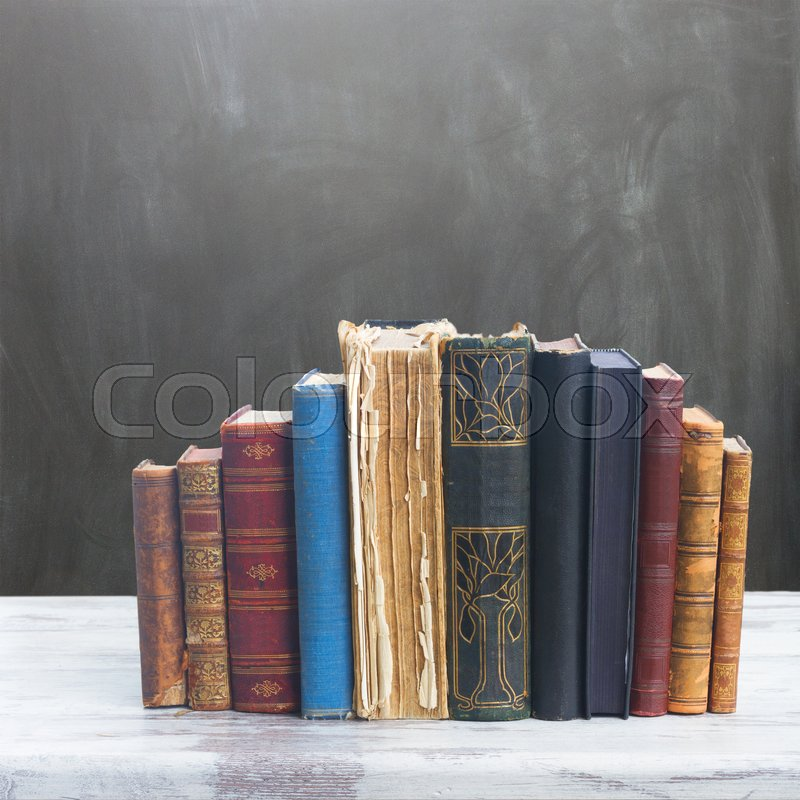 Stock image of 'set of books on white wooden desktop, empty blackboard in background'