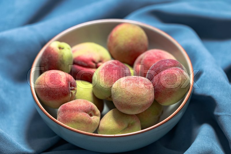 Stock image of 'Vineyard peach in gray bowl on blue background'