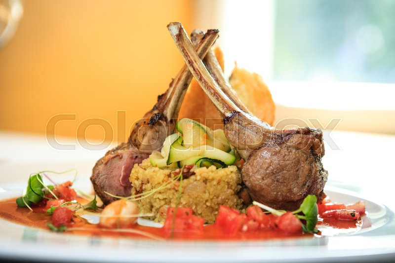 Stock image of 'Grilled lamb served on cous-cous with sun dried tomatoes and raisins, goat cheese pastry and smoked tomato and butter sauce'