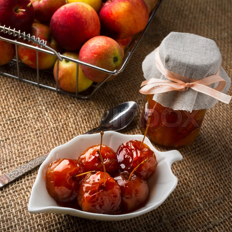 Stock image of 'Cherry apples covered in syrup on white saucer, spoon, jar of homemade marmalade and apples in metal wire basket on a table covered with burlap, square. Selective focus. The toning'