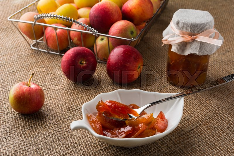 Stock image of 'Homemade apple jam on white saucer, spoon, jar of marmalade and apples in metal wire basket on a table covered with burlap. Selective focus. The toning'