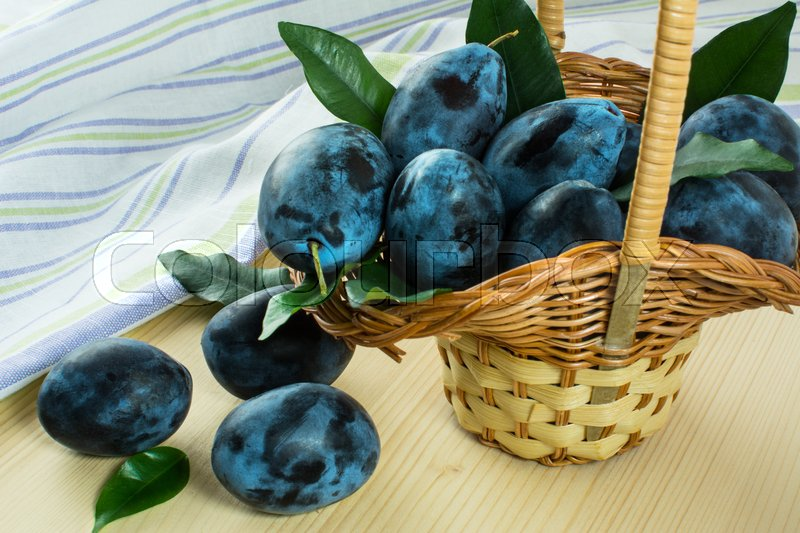 Stock image of 'Ripe plums green leaves in small wicker basket on light wooden table with linen striped towel. Selective focus'