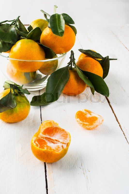 Stock image of 'Ripe mandarines with leaves in a glass bowl on a white wooden background selective focus vertical'