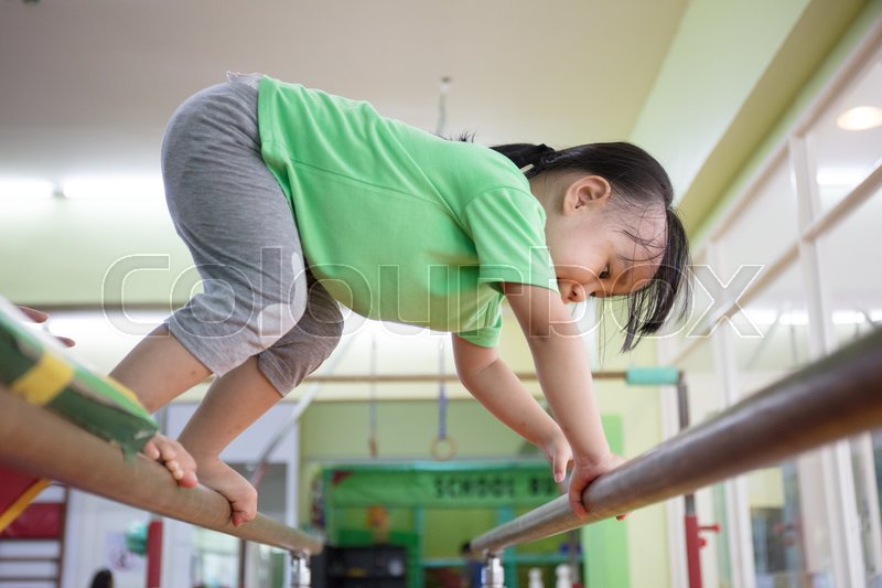 Stock image of 'Asian Chinese little girl climbing on parallel bars at indoor playground'