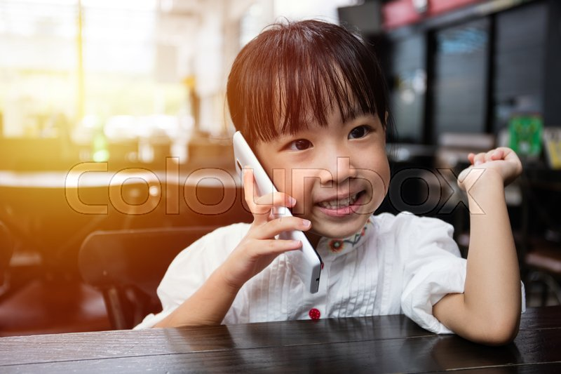 Stock image of 'Asian Chinese little girl playing smartphone at outdoor cafe'