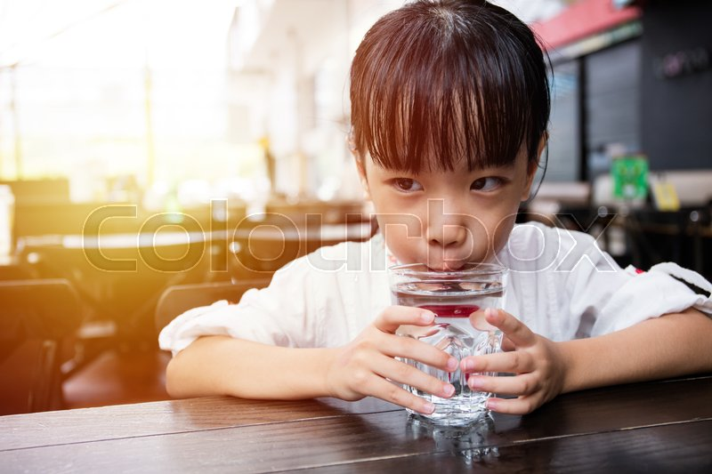 Stock image of 'Asian little Chinese girl drinking water in outdoor cafe'