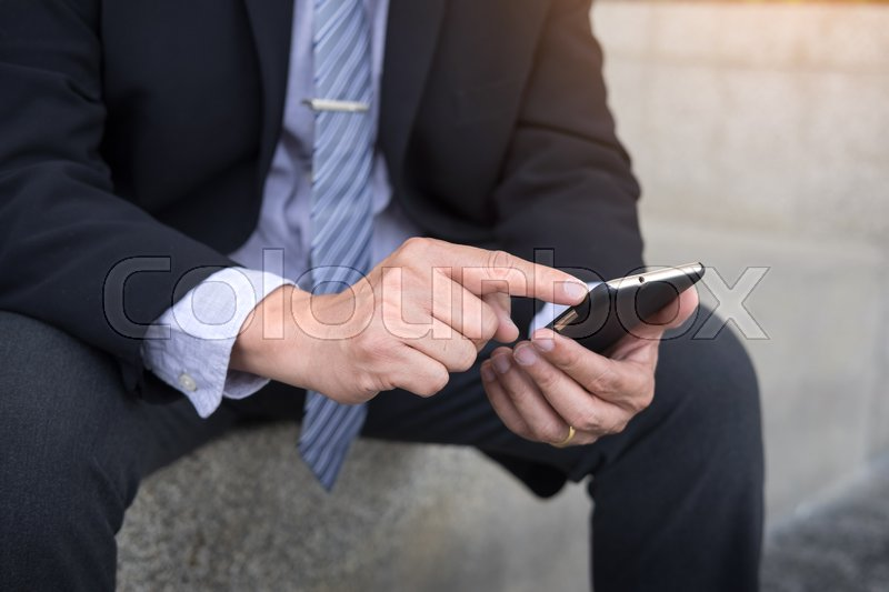 Stock image of 'business man wearing black suit and using modern smartphone in outdoor.'