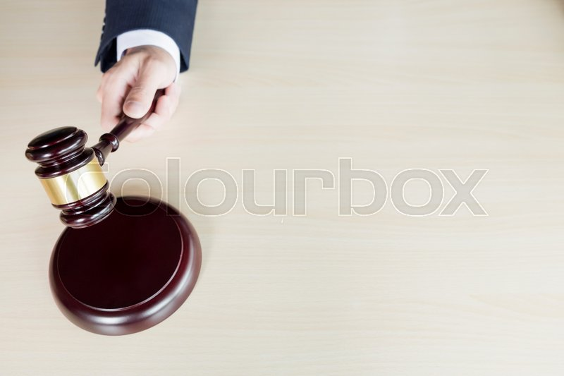 Stock image of 'hand of Judge's holding wooden hammer knocking a gavel against wooden background.'