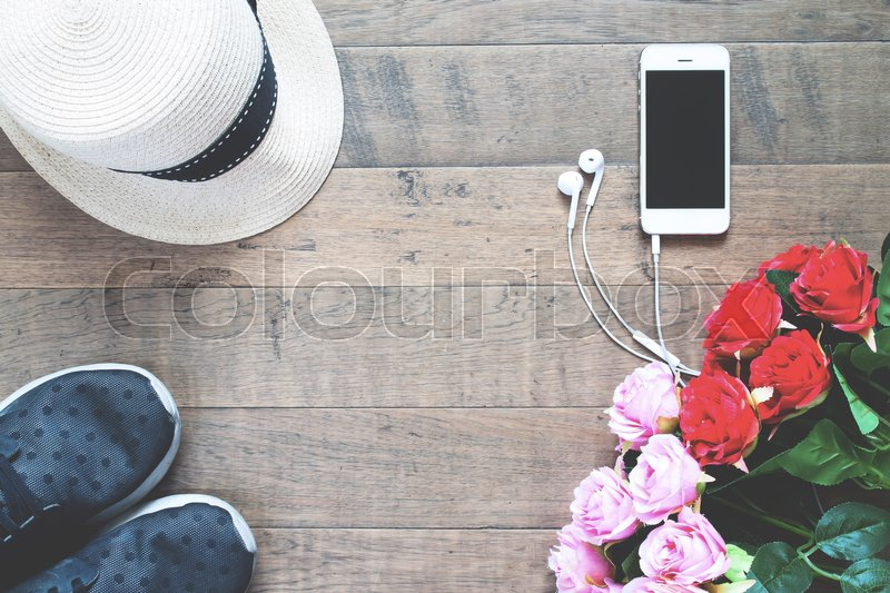 Stock image of 'Smartphone with red and pink roses, hat and sneaker on wood floor with copy space'