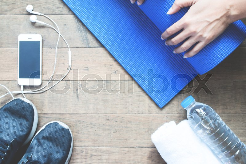 Stock image of 'Woman hand folding yoga mat on wood floor, Workout with technology concept'