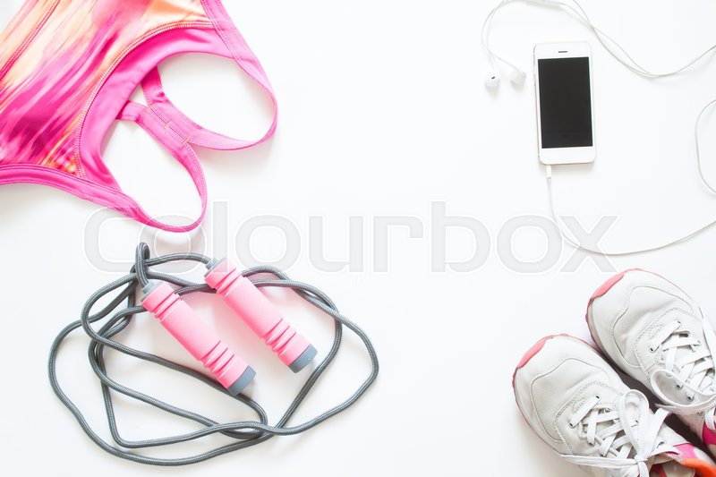 Stock image of 'Flat lay of cellphone, pink sport bra, jump rope and sneaker on white background, Working out and healthy concept, top view'