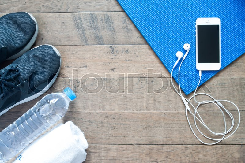 Stock image of 'Overhead view of smartphone with earphone on blue yoga mat with black sneaker, bottle of water and towel. Fitness and workout concept with copy space'