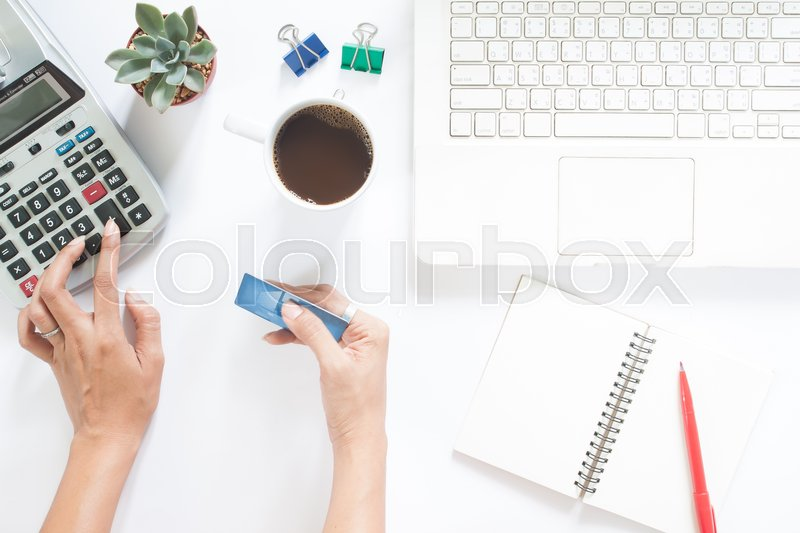 Stock image of 'Overhead view of woman hand using calculator and holding credit card with laptop and stationery on white table'