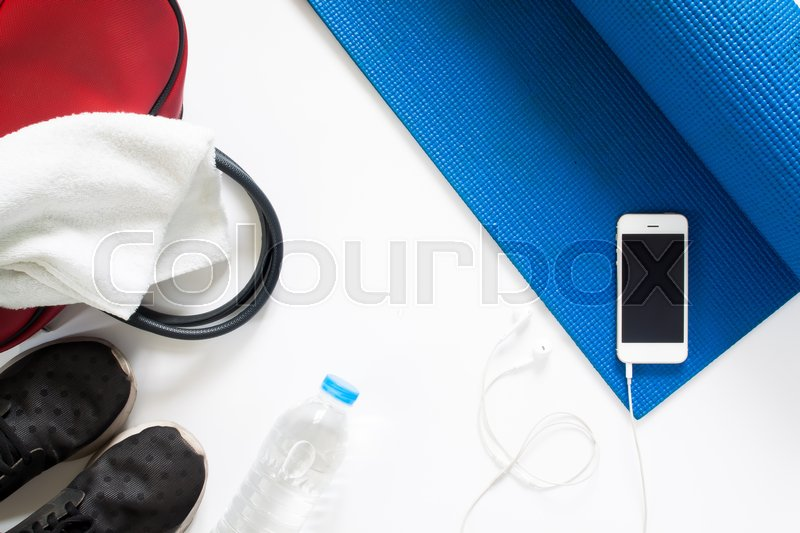 Stock image of 'Overhead view of yoga concept with bottle of water, sneakers, towel, bag and smartphone on blue yoga mat on white background, Isolated on white with copy sapce'