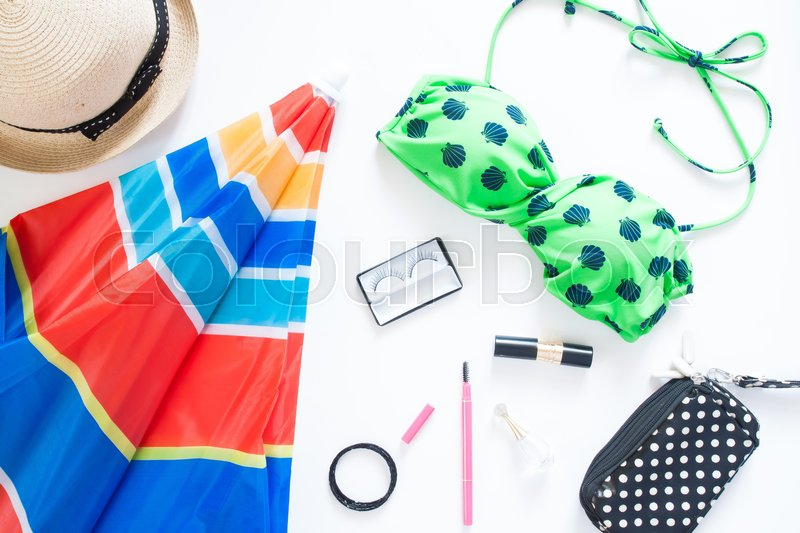 Stock image of 'Flat lay of summer fashion with green color swimsuit, colorful beach umbella and girl accessories on white background'
