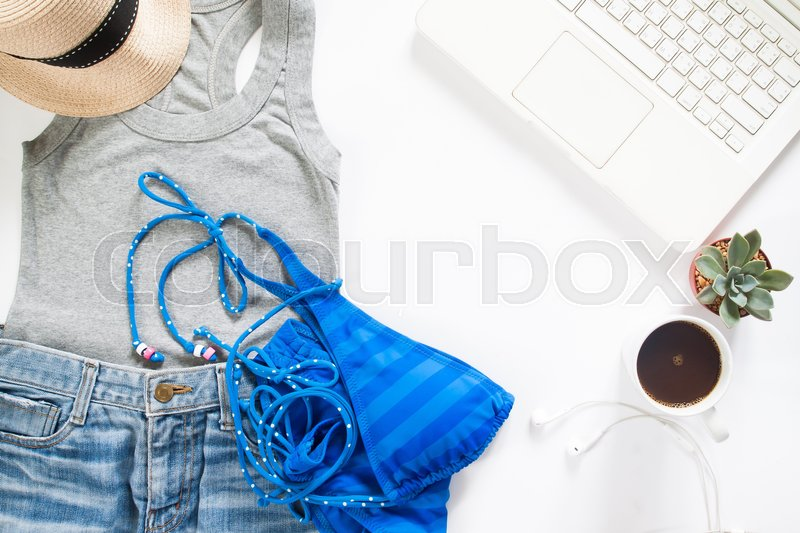 Stock image of 'Flat lay of summertime clothing with blue stripe bikini, laptop and cup of coffee on white background'