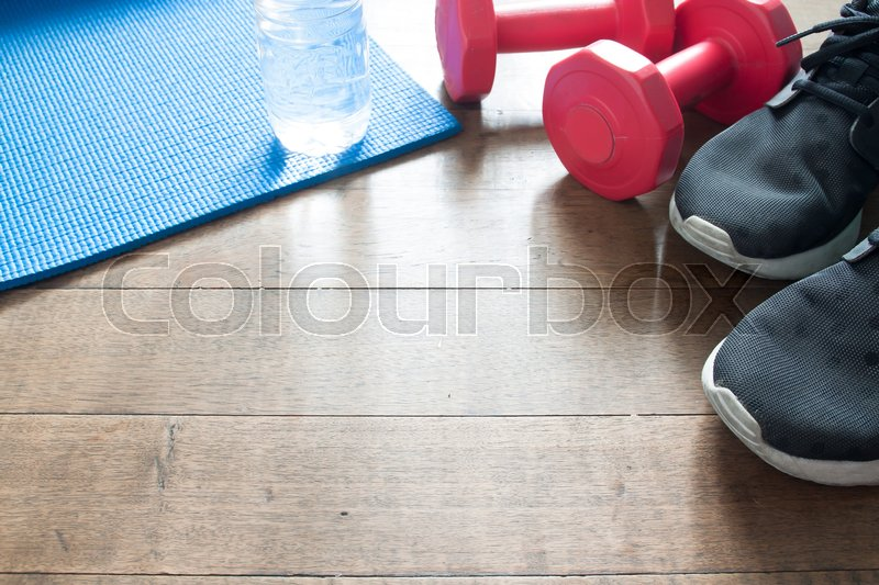 Stock image of 'Sport equipments on wooden floor, red dumbbells, sneaker and bottle of water on yoga mat'